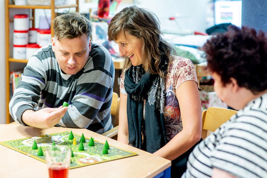 Mitarbeiterin mit Nutzer*innen haben viel Spaß bei einem Brettspiel.